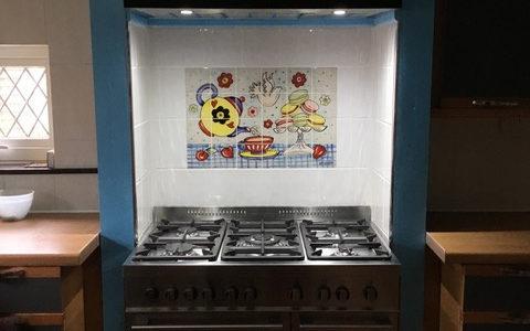 Afternoon tea tile mural behind range cooker in kitchen