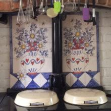 Flowers in vases tile mural behind Aga range cooker