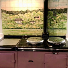 Green wood tile mural behind Aga range cooker