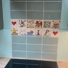 selection of hand painted tiles on cooker splashback